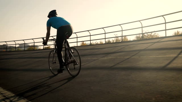 Young male cyclist cycling on track outdoors