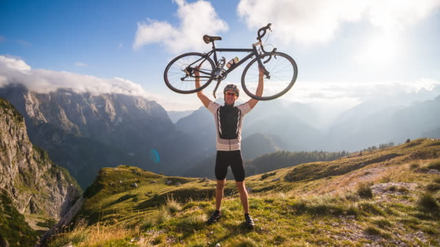 Young male cyclist victoriously raising bike on top of mountain