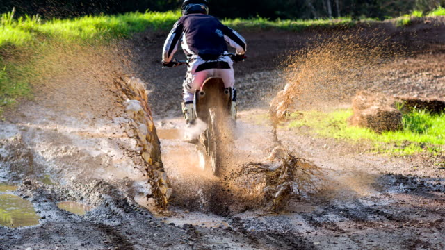 Young male motocross rider driving through a puddle of mud