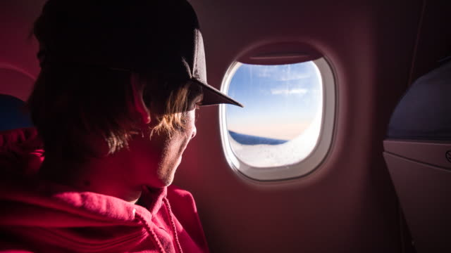 Young male passenger looking through airplane window during flight