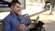 Young male professional reading newspaper and loosening tie on bench at train station