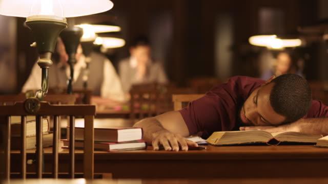 DS jonge mannelijke student inslapen over boeken in de bibliotheek