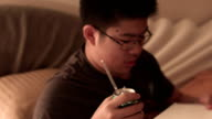 A Young Male Teenager Drinking Soda in Bed at Night