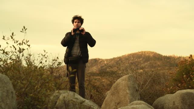 Junger Mann, 25 Jahre alt Reisen Hipster, Naturbeobachtung mit Fernglas aus der erhöhten felsigen Punkt in der Nähe von Devil Dance Floor im Yosemite National Park