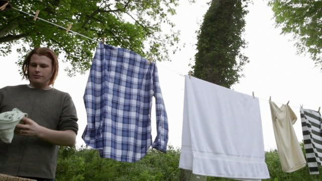Young man and son taking clothes from washing line