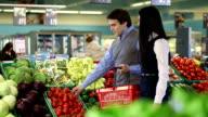 Junger Mann und Frau kaufen Gemüse