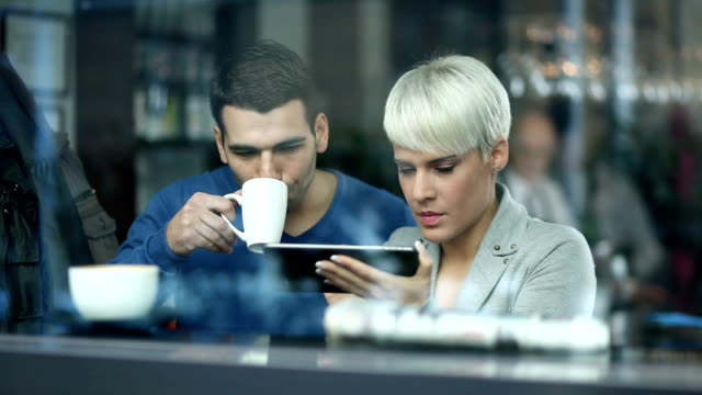 Young man and woman drinking coffee and using tablet