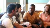Giovane uomo e donna spiegando qualcosa per gruppo di amici