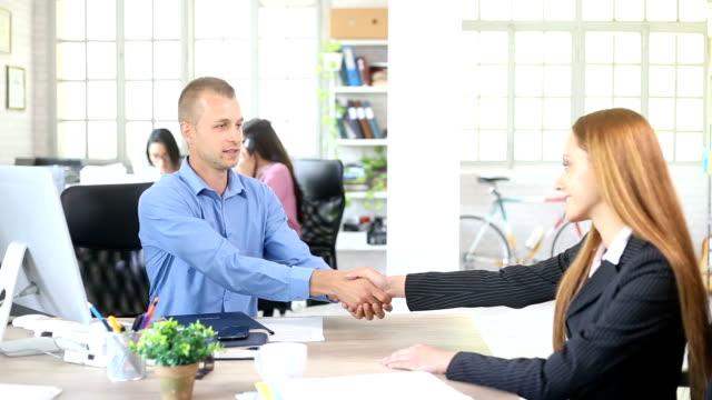 HD ung man och kvinna undertecknandet av avtal i moderna kontor