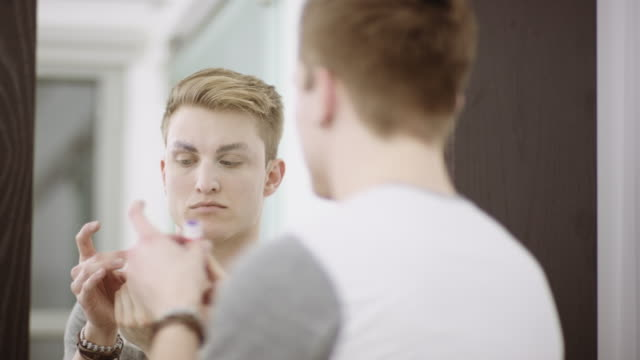Young man applying glue to eyebrows