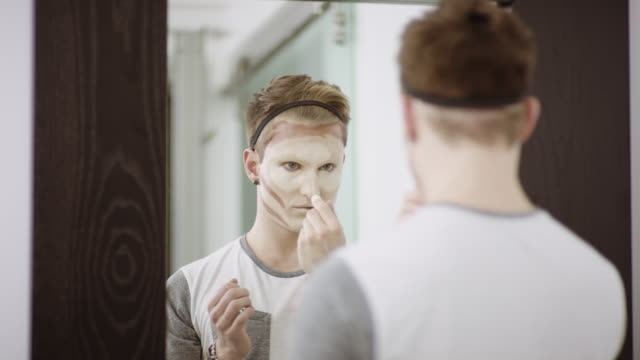 Young man applying makeup in front of mirror