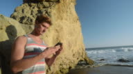 WS Young man at beach on phone, taking pictures / Malibu, California, United States