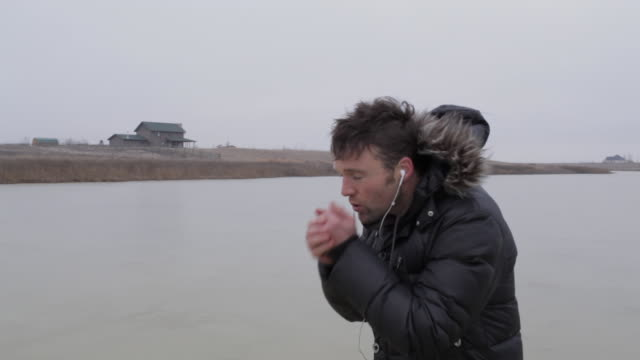 Young man blowing into his hands on frozen pond in winter in rural Montana, USA.