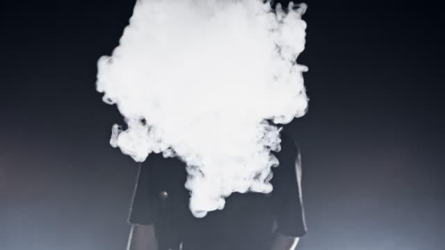 MS Young man blowing smoke at the camera