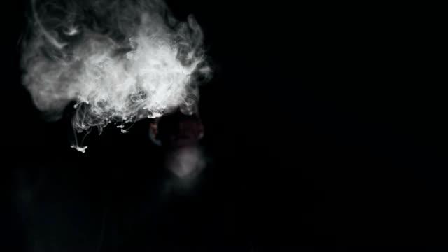 SLO MO Young man blowing smoke ring
