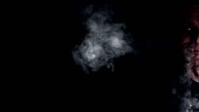 SLO MO Young man blowing smoke through nose and mouth