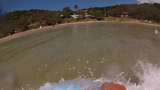 Young man bodyboarding in Byron Bay, Wategos Beach and screaming