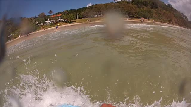 Young man bodyboarding in Byron Bay, Wategos Beach, slow motion