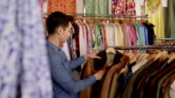 MS A Young Man browses through a rack of colourful vintage clothing