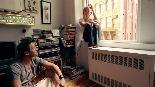 MS, Young man browsing records, woman with headphones sitting on  window sill, New York City, New York, USA