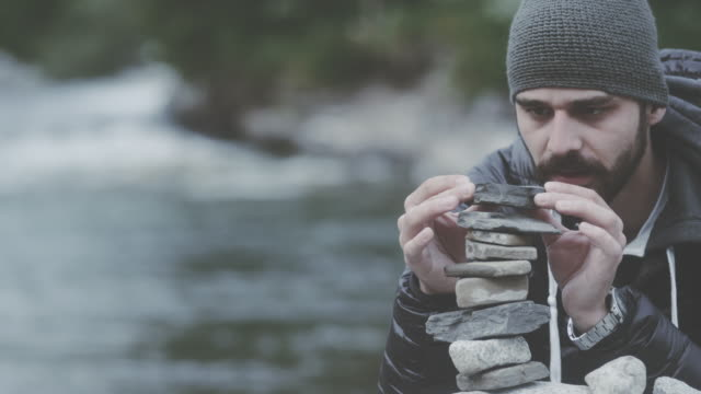 Young man building tower of rocks by the river. Looking for balance