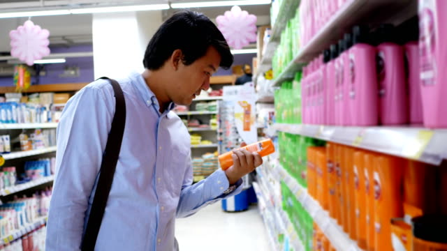 young man buying shampoo in shopping mall