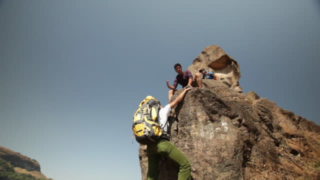 Young man climbing rock with his friend helping him