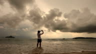 Junger Mann hand-frame-Zusammensetzung auf dem sunset beach