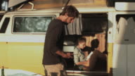 Young man cooking dinner for girlfriend in campground outside in front of VW bus in sunshine at Atlantic Coast in France