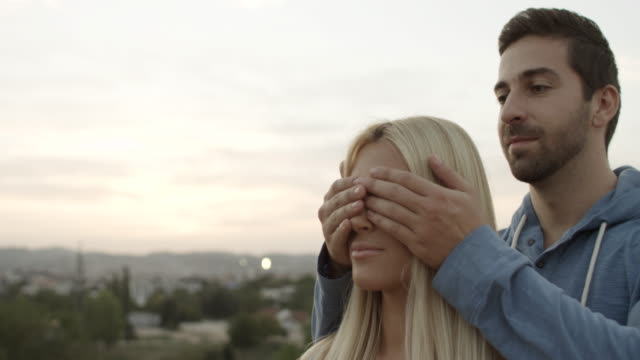 Young man covering the eyes of surprised girlfriend