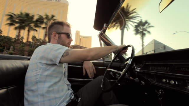 A young man cruises in a convertible down a quiet, palm-lined street in Las Vegas.