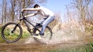 SLO MO Young man cycling through a puddle