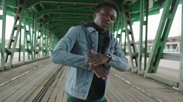 Young man dancing under the bridge