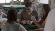 Young man deals cards to friends in competitive card game