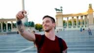 Jonge man ontdekken grote stad en nemen selfie in de buurt van monument