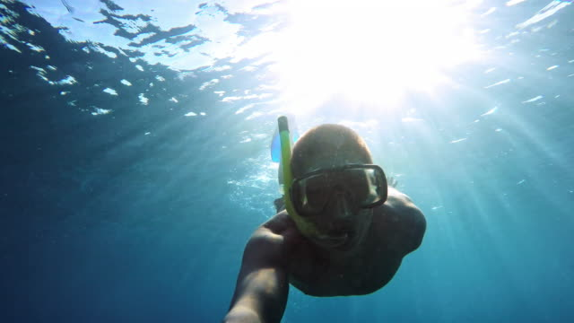 POV Young man diving with snorkeling mask
