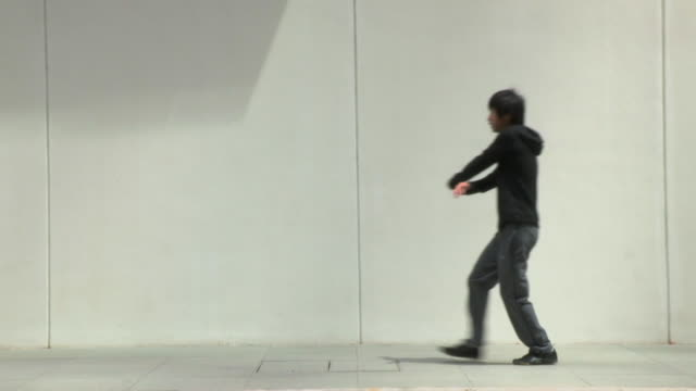 WS SLOMO Young man does backflip from standing position in street/Singapore