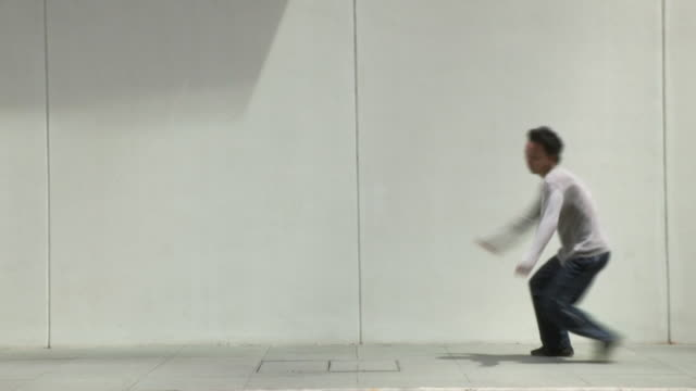 WS SLOMO Young man does spinning jump and rolls in street, Parkour/Singapore