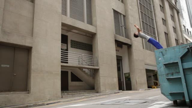 Young man doing backwards somersault off of dumpster skip Parkour/Singapore