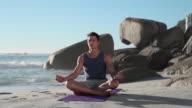 Young man doing yoga on beach