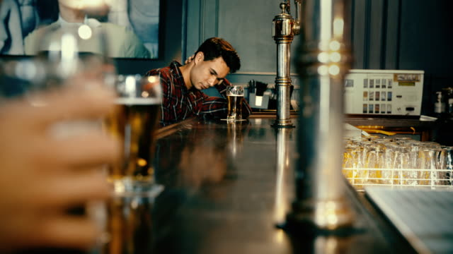 Young man drinking alone in a bar