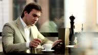 Junger Mann, trinkt Kaffee und mit tablet