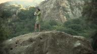 WS Young man drinking water on rock / Malibu Creek, California, USA