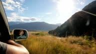 Young man drives down 4x4 road admiring mountain view along the way