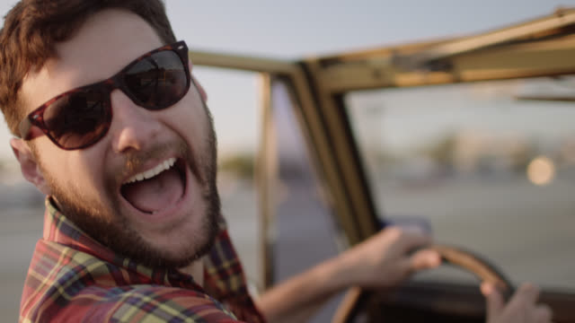Young man driving classic Ford Bronco laughs with friends on road trip and waves at passing tractor trailer