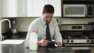 MS Young man eating breakfast and using digital tablet sitting in kitchen / Orem, Utah, USA