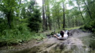 Young man falling down from the mountain bike into the dirty puddle.