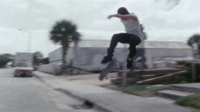 Young man filming skater kickflipping off steps and wiping out in street