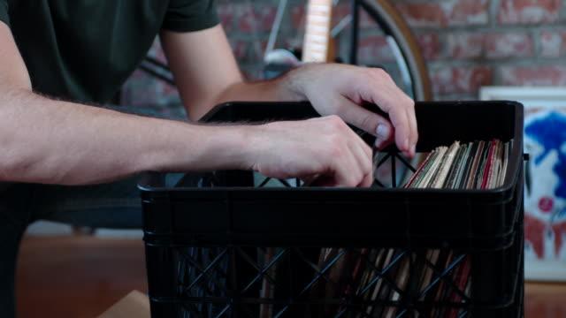 Young Man Flips through Vinyl Record Collection