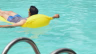 Young man floating on inflatable bed in the swimming pool, Delhi, India